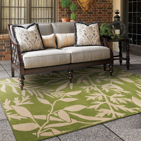 green outdoor area rug with palm leaves under an outdoor tommy bahama love seat