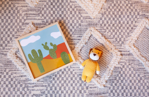 stuffed lion and framed cacti print on top of a grey and white moroccan rug.