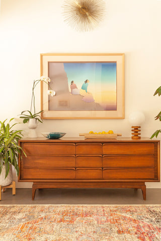 native american water color hangs on the wall above a mid century modern wooden credenza. On the floor is a muted tribal area rug.