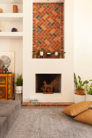 stucco fireplace with brick mantel. hand carved Polynesian horse figure on the fireplace with two large neutral pillows on the floor. A black and white modern area rug is on the floor in front of the fireplace.