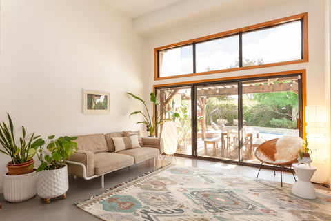 ikat blue and ivory area rug on acid washed concrete floors. Large sliding doors against the back wall with a tan sofa and chair positioned around the rug.