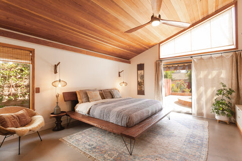 area rug under king sized bed in modern bedroom. Wooden tongue and groove arched ceiling and big sliding glass doors leading out to a patio.