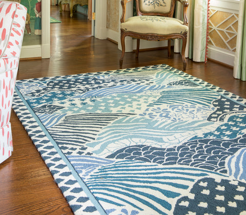 blue chinese inspired area rug in a french country living room