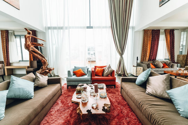 A large room with a floor to ceiling window. Two beige couches sit across from eachother with a wood table in the center. To the back of the table are two club chairs: One blue, one red. Below all of the furniture is a bright red area rug.