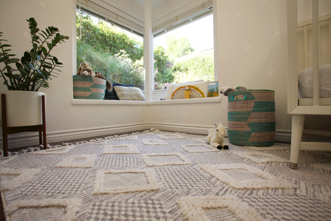 corner of a nursury with a big window. white modern crib, floor plant and a grey and white diamond patterned rug on the floor.