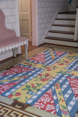 floral rug at the foot of a country cottage stairs.