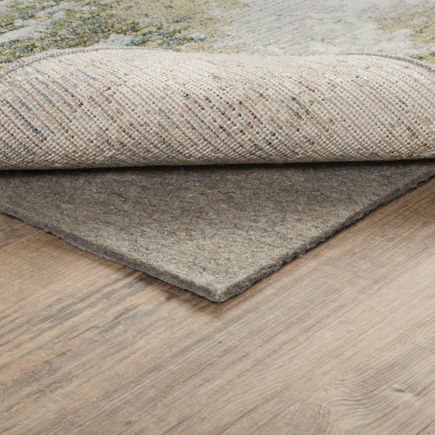 A beige area rug is folded upwards to expose a rug pad underneath.