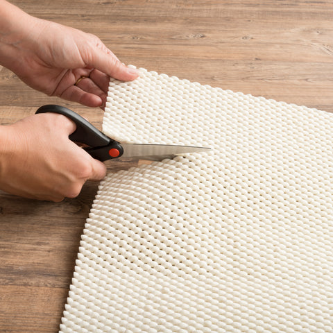 woman cutting rug pad with scissors