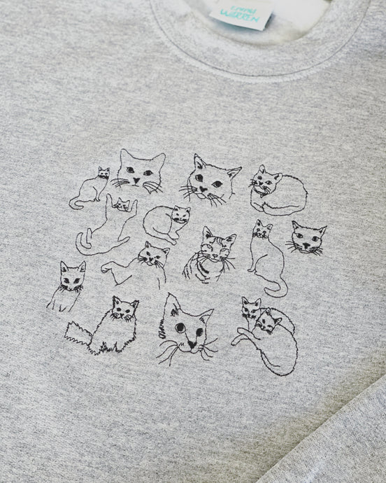 Cat doodle embroidered sweater with heart cat sleeve detail