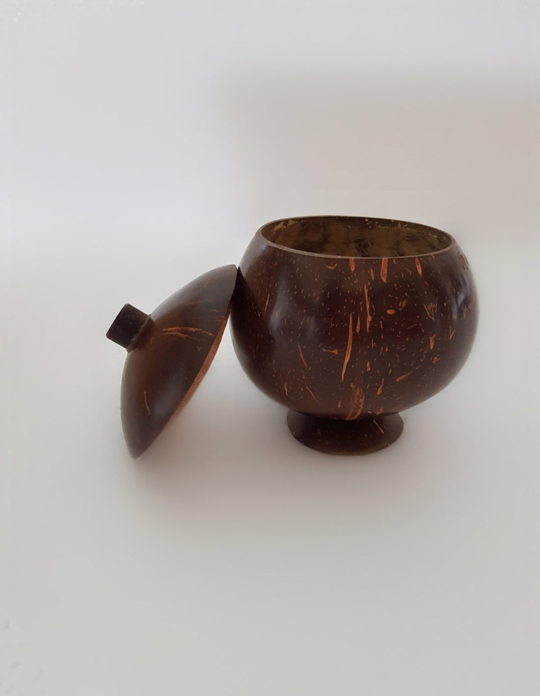 A hand polished coconut bowl with a lid.