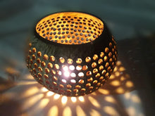 A coconut shell lamp lit by a candle
