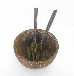 A set of a natural look bowl with utensils inside the coconut bowl