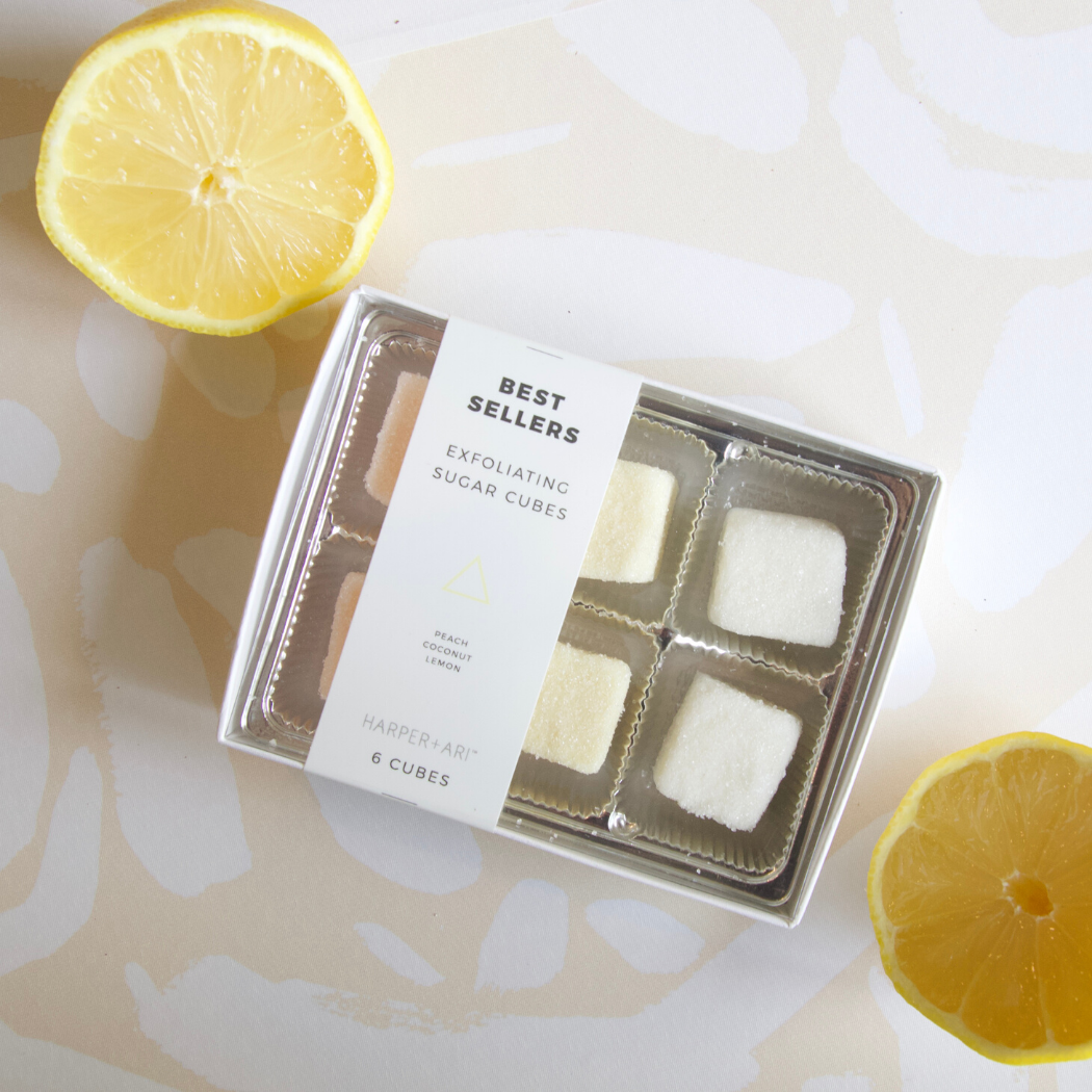 Against a neutral patterned background and surrounded by lemon slices are neutral colored sugar cubes in a pack of six with a white harper + ari best sellers label