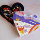6 oz heart-shaped truffle box sits on a blush surface with the lid off, revealing the truffles inside.