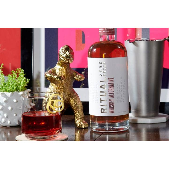 Glass bottle with white label that reads ritual zero proof whiskey alternative sitting on a table next to a mixed drink and decor