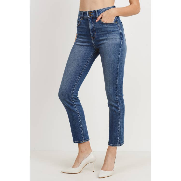 Side view of model wearing medium wash blue denim straight jeans with a double button fly paired with white heels