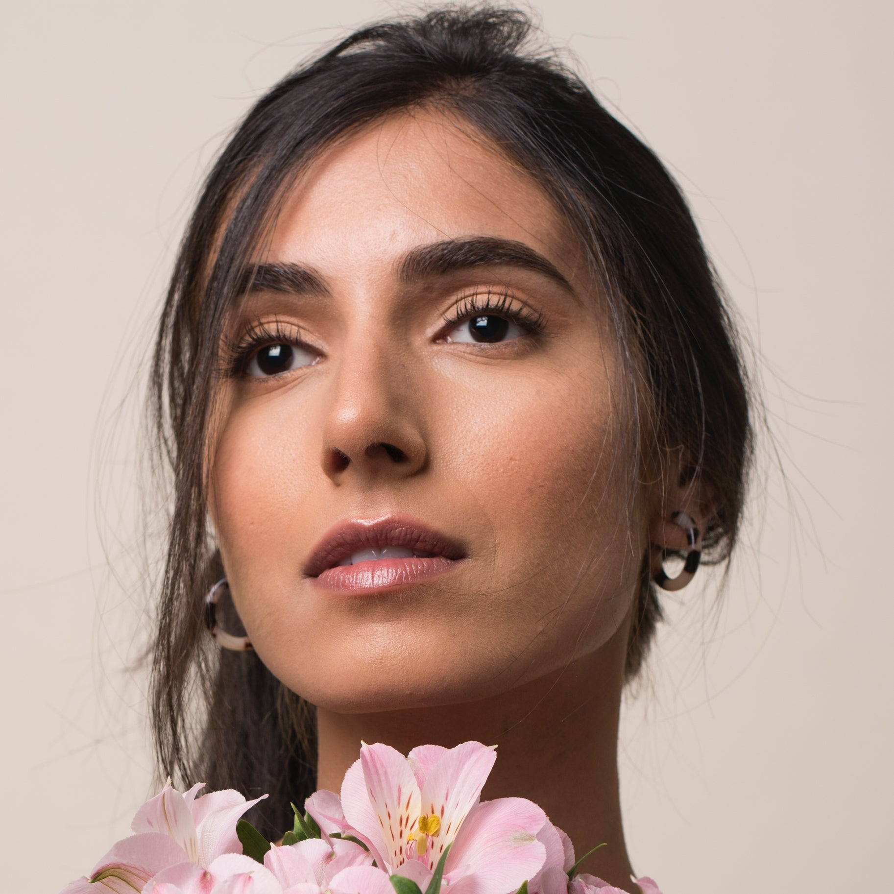 Brunette model facing camera wearing blonde tortoise hoops and holding pink flowers