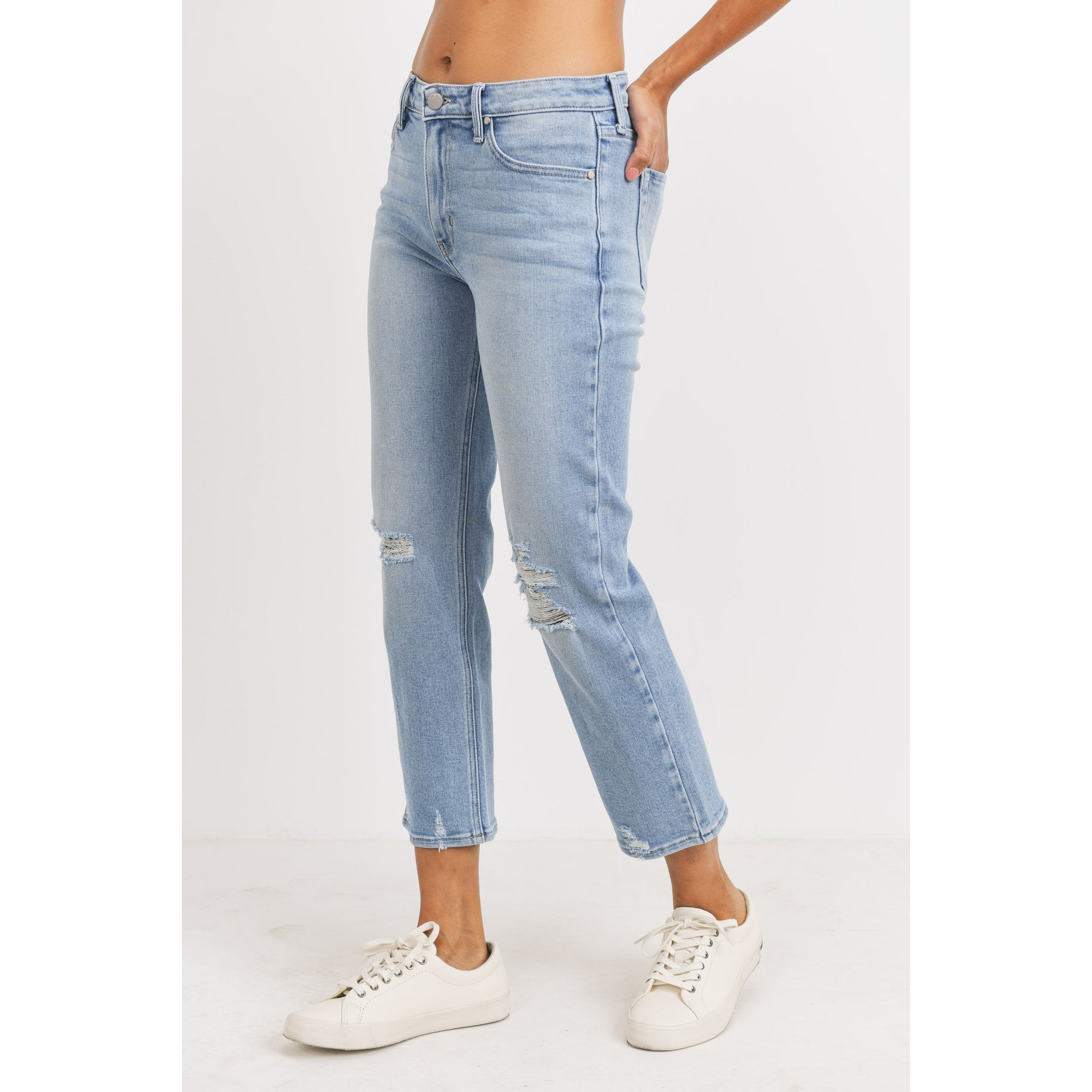Side view of model wearing the light wash straight jeans. There is distressing at the knees and parts of the hem. Her hand is in the back pocket and she is wearing white sneakers