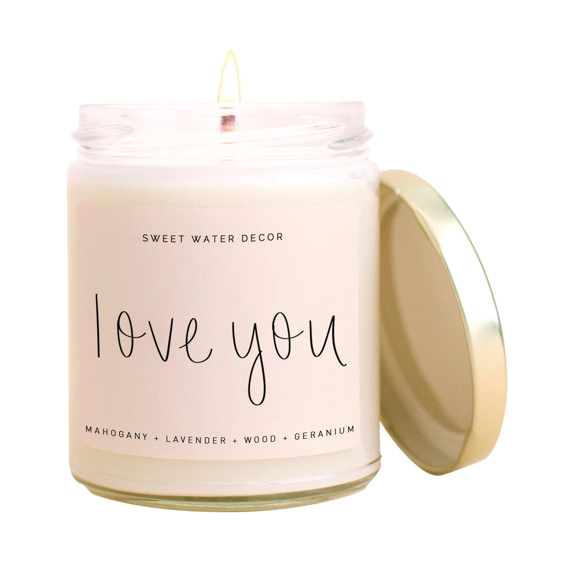 "Clear glass candle filled with white soy wax with a lit wick. The gold lid is propped against the side of the jar. The blush pink sweet water decor label reads ""love you"" in a tin black cursive font"