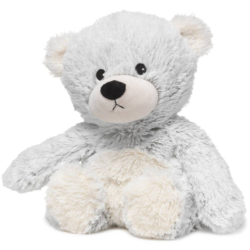 Very light powder blue fluffy teddy bear with a white nose, tummy, feet, and ears sits upright in front of white background. It has a black nose and black eyes