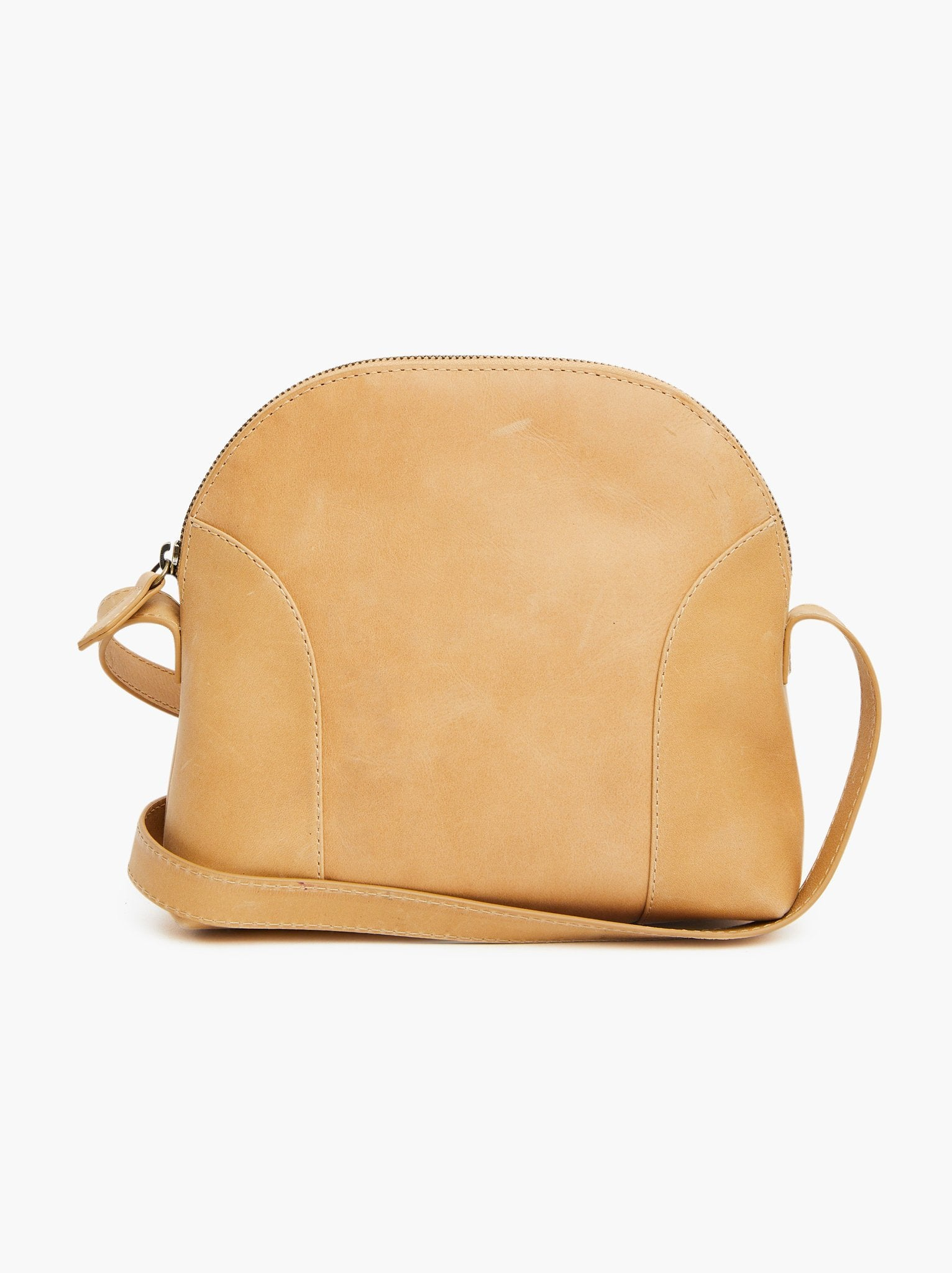 Fawn colored dome shaped leather bag shown against white backdrop with crossbody strap laid around it