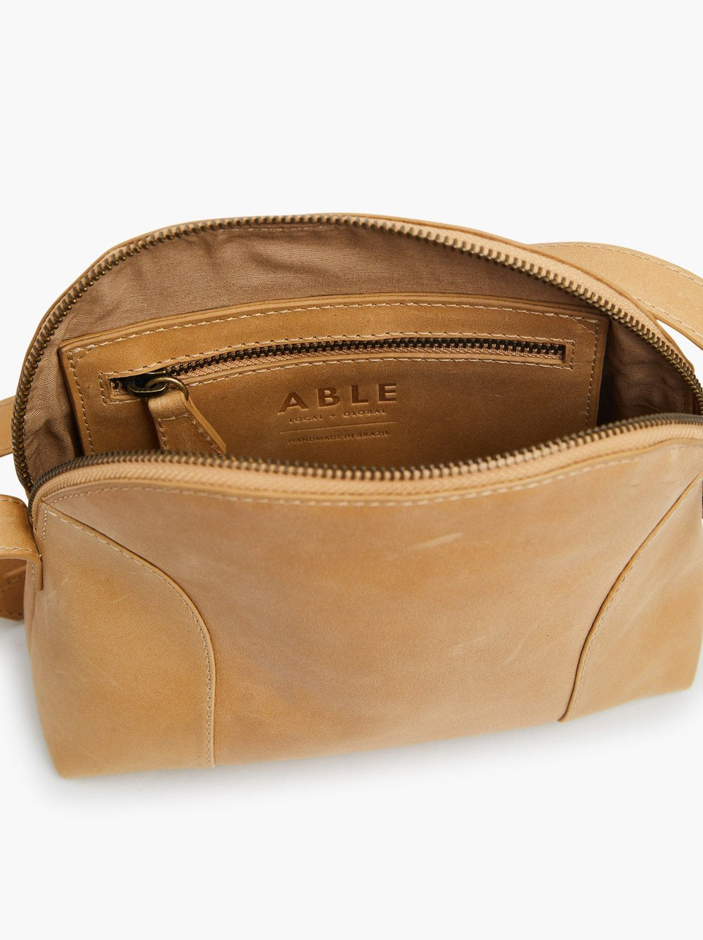 Unzipped view of inside the fawn dome shaped bag revealing the interior zipper pocket and the ABLE logo