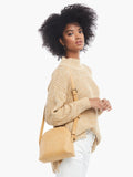 Model wearing the dome-shaped crossbody bag in fawn color over her shoulder, styled with a chunky tan sweater and white jeans