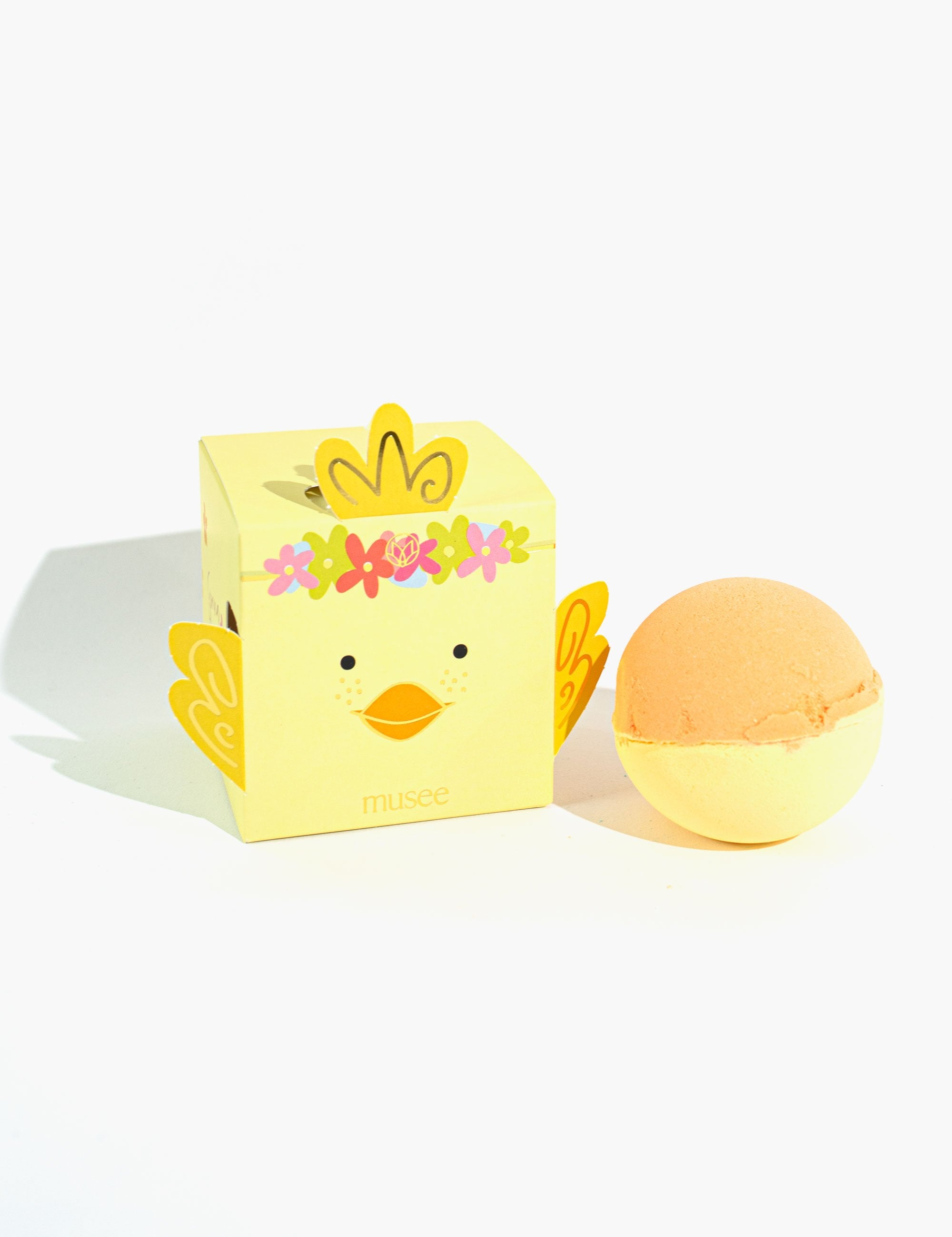 Yellow cube box with a baby chick face and wings sits over solid white surface next to a yellow and orange colored spherical bath bomb