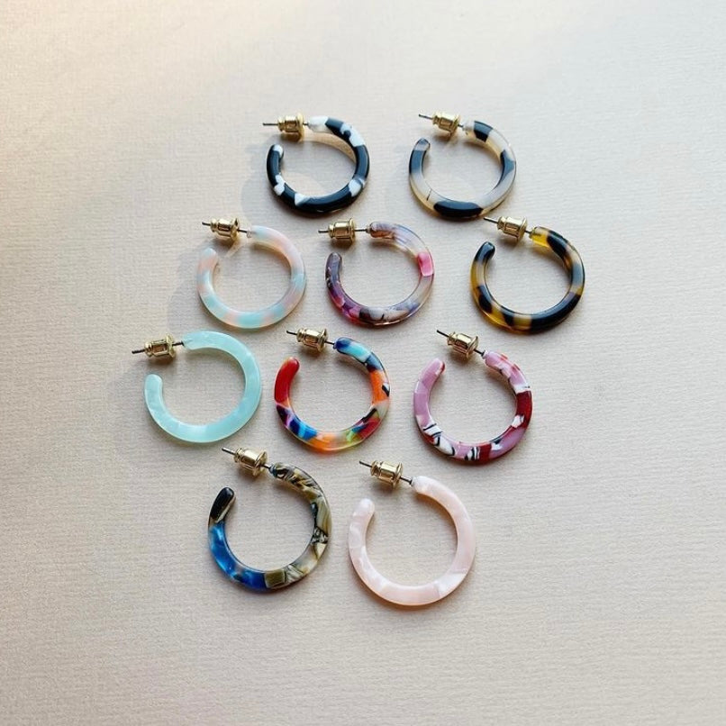 A variety of ten printed design hoop earrings of the same size and shape lay arranged on a beige surface.