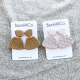Two pairs of earrings, each with two clay trapezoid pieces connected by a piece of gold hardware. Each pair is on its own white beckhillco card