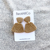 Tan colored trapezoid earrings with a geometric pattern on one of the clay pieces over fabric background