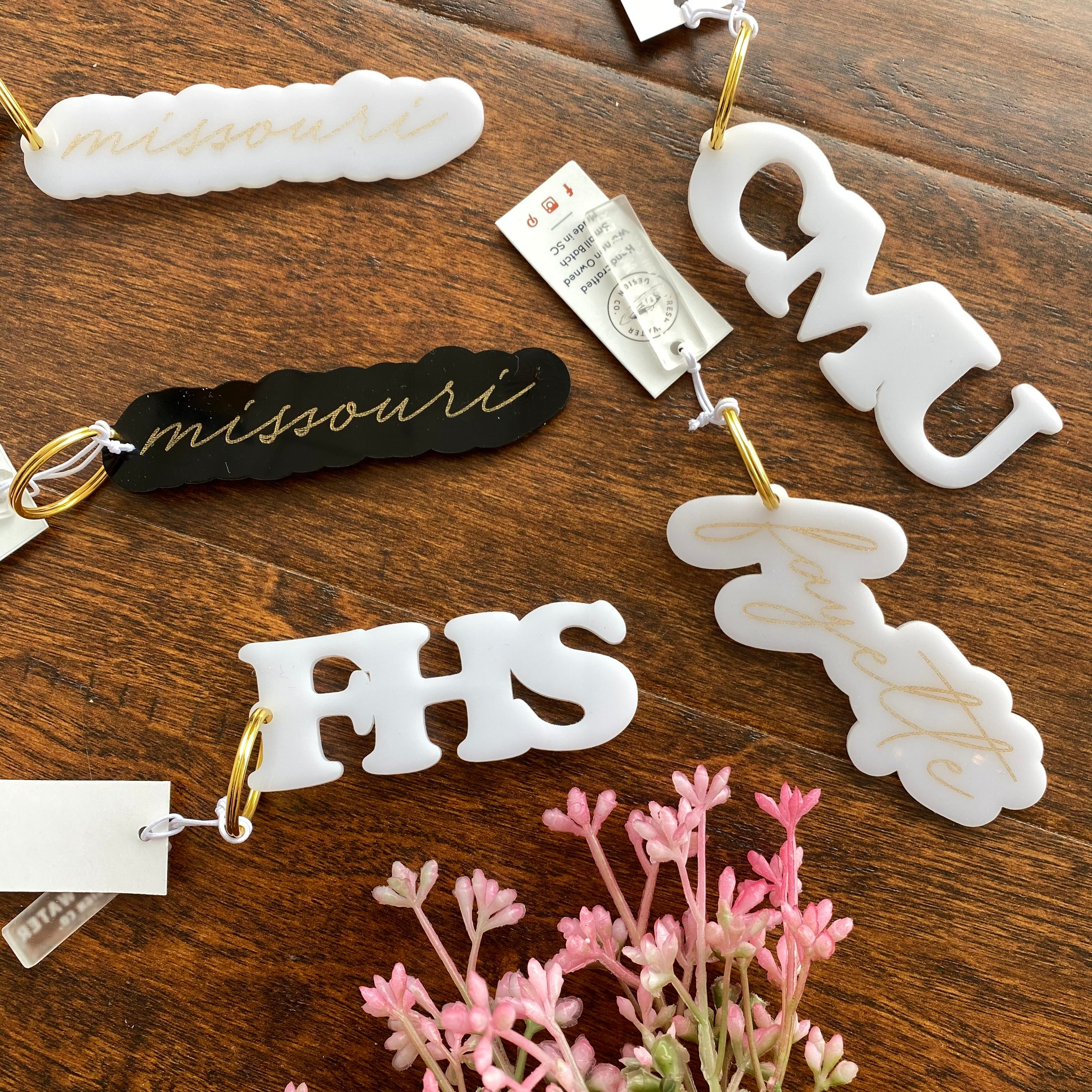 White missouri, black missouri, CMU, FHS, and Fayette acrylic keychains sit together on wood surface with pink florals