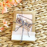 Cardboard packaging with an image of a friendship bracelet stack wrapped in a striped ribbon sitting in a basket