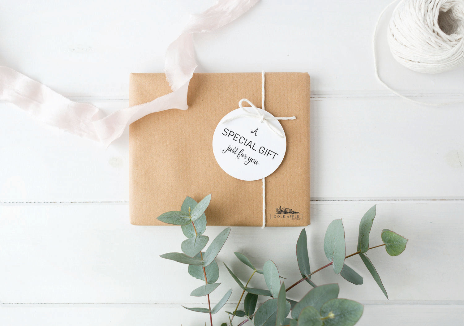 Brown rectangular packaging wrapped in white string with a white tag that reads a special gift just for you. Gift sits on white painted wood surface surrounded by ribbon and eucalyptus branches