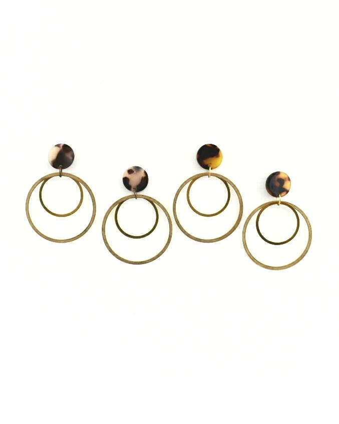 Two pairs of double hoop gold earrings, each with a tortoise drop above the hoops. One white tortoise, one traditional tortoise
