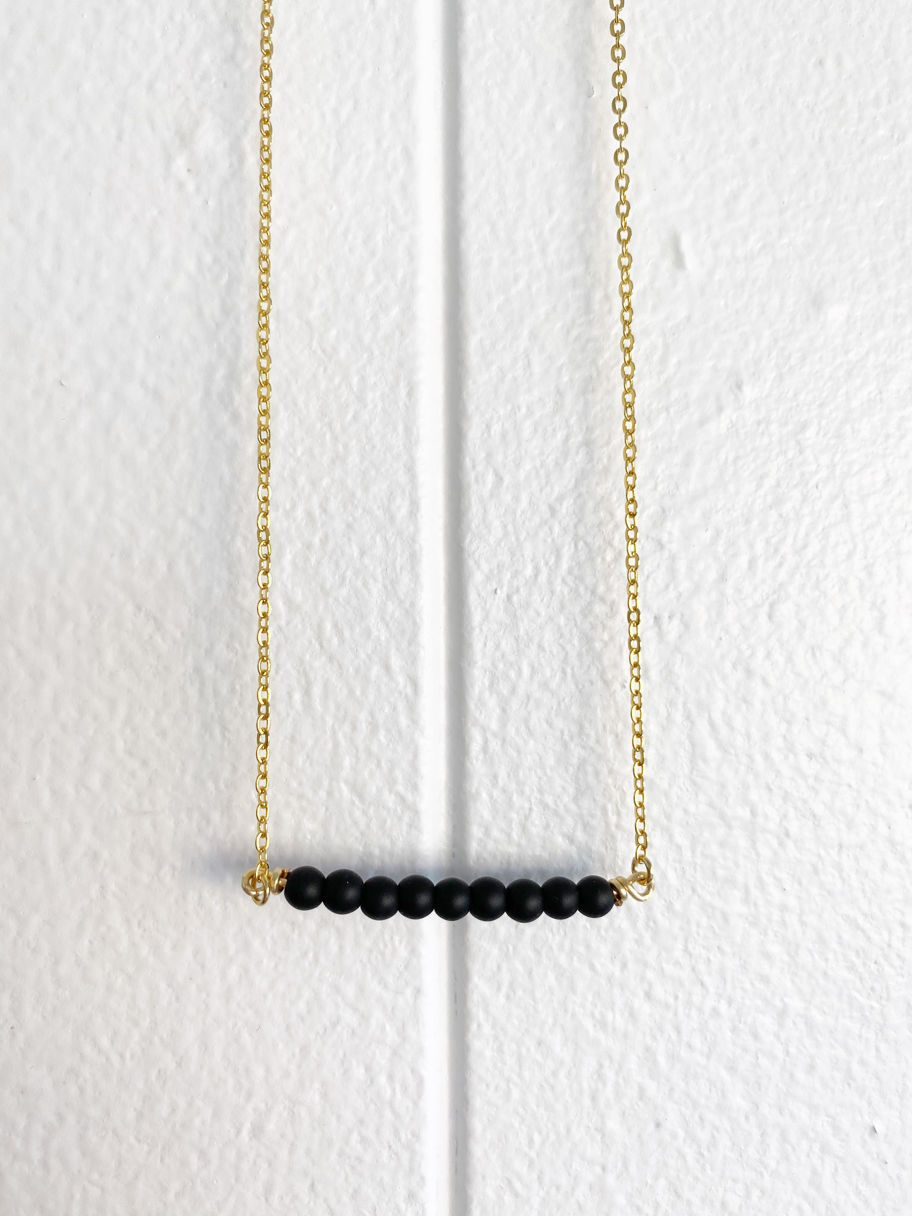 Against a white paneled wall hangs a gold chain necklace with black round beads that form a horizontal bar shape.
