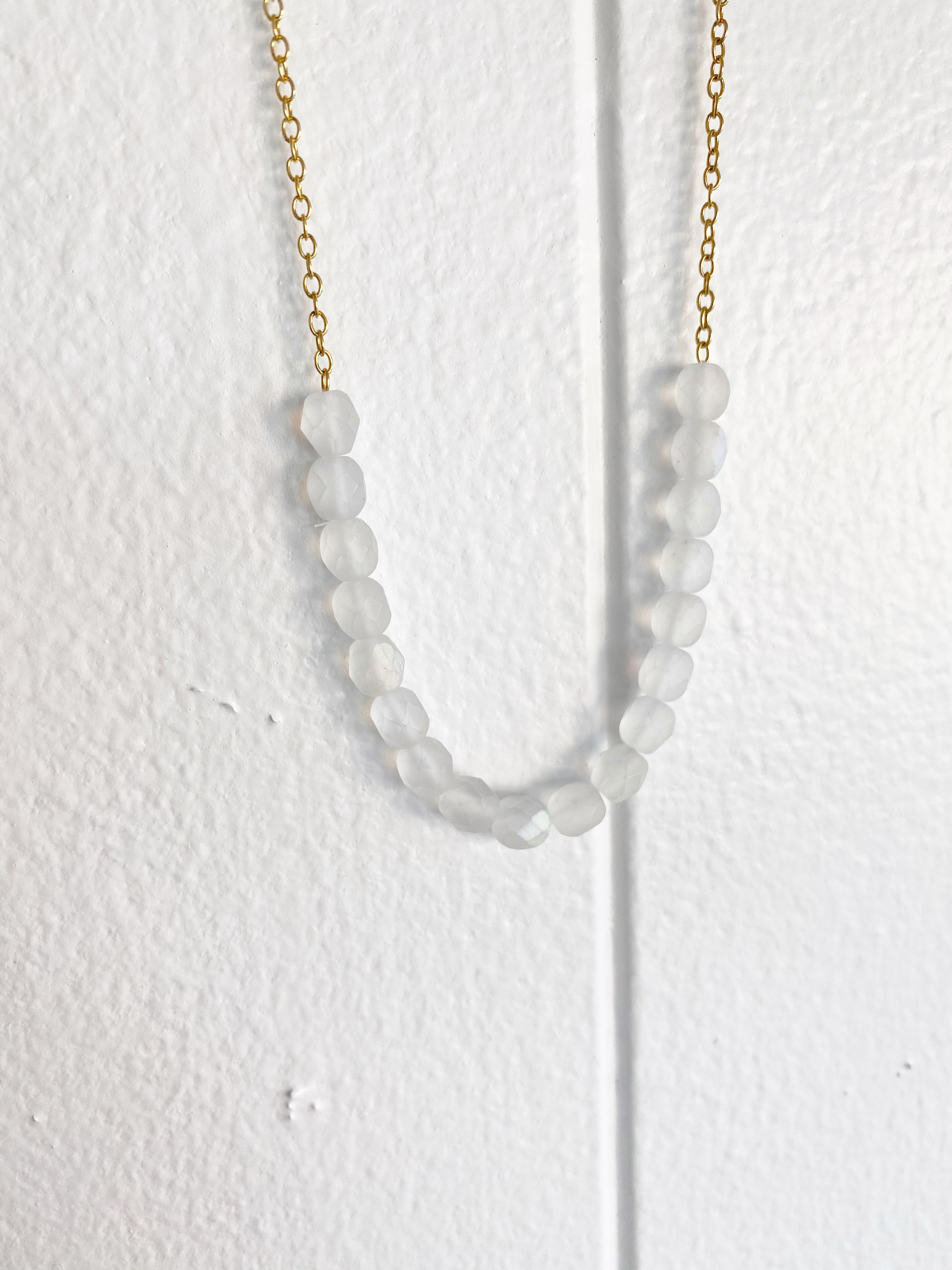 Geometric cloudy white beads make up focal point of gold chain link necklace