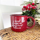 "Red mug with white and black speckles sits on wicker chair next to christmas greenery. The mug has ""a thrill of hope, the weary world rejoices"" written on it in white cursive script"