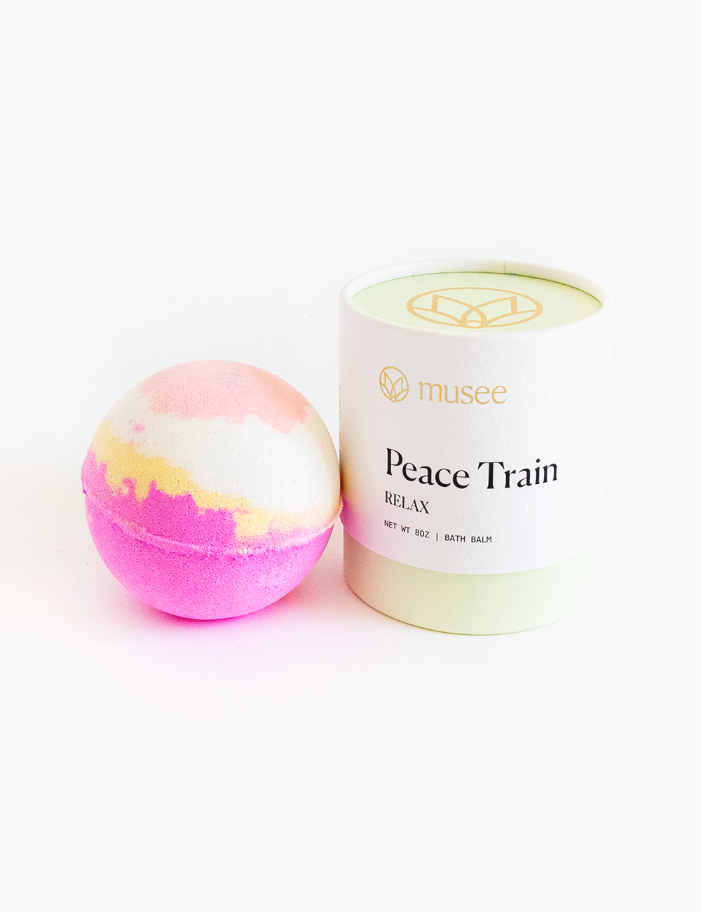 Cylindrical packaging is a muted green color with a white musee peace train label. Next to the packaging is an unpackaged bath bomb. It is pastel pink on top, yellow in the middle, and hot pink on bottom of spherical shape.