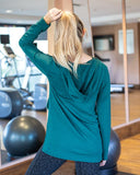 Back view of blonde model standing in a gym wearing green v-neck faux-wrap hooded sweatshirt