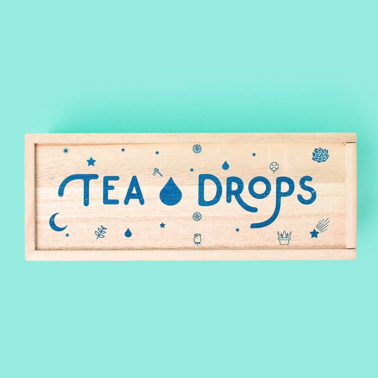 Light unstained wooden rectangle box with blue tea drops logo and little graphic designs on the front. Sitting against a solid teal surface