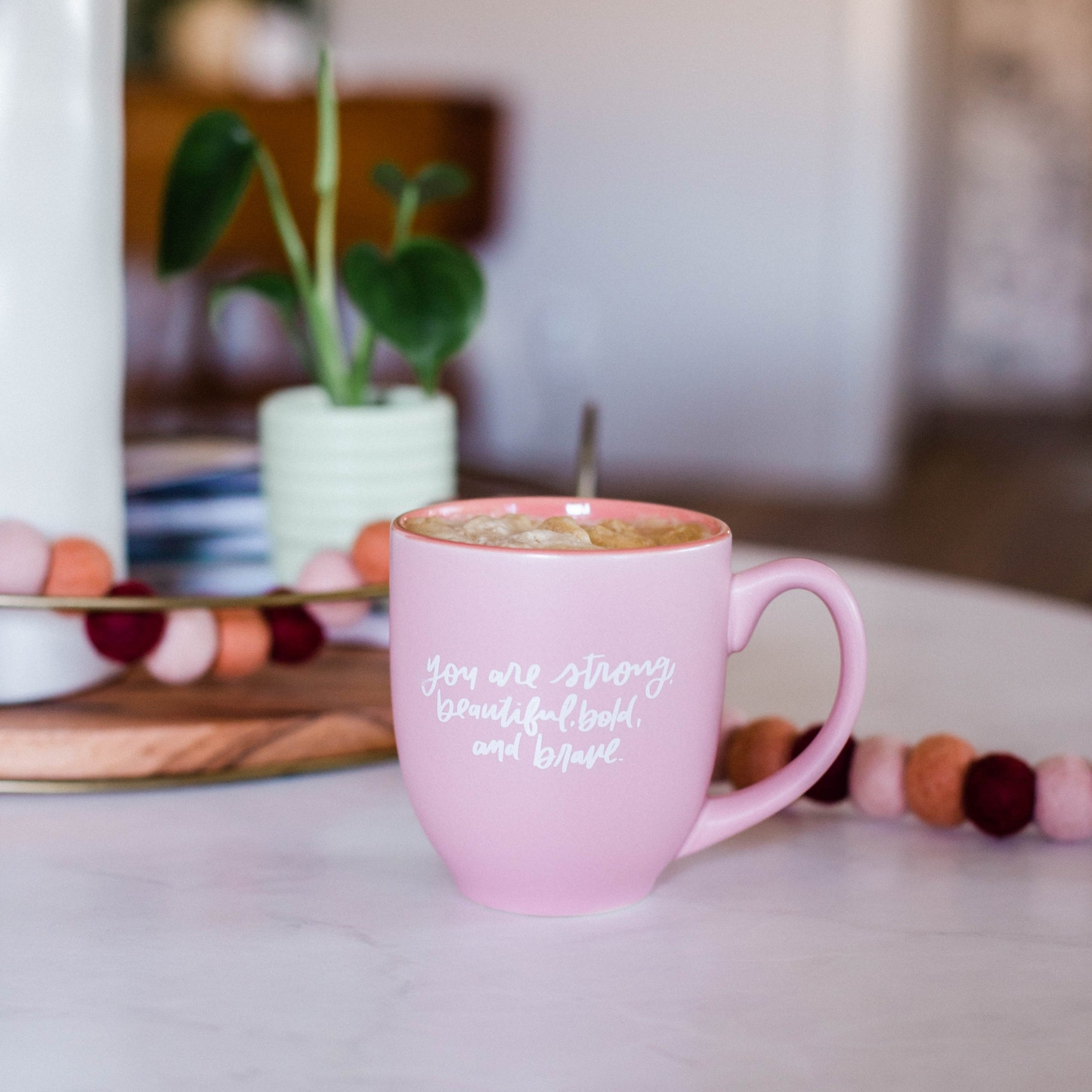 "Pink ceramic mug filled with coffee sitting on a white marble countertop surrounded by pink garland, greenery, and home decor. The mug has white cursive script that reads ""you are strong, beautiful, bold, and brave"""