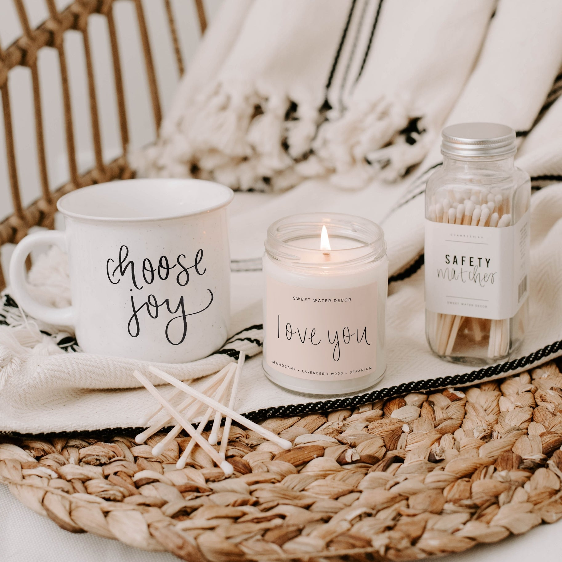 Clear glass candle filled with white wax with a blush pink love you label burns while sitting on a throw blanket next to safety matches and a white mug