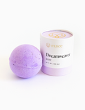 Cylindrical packaging is a muted purple color with a white musee Dreamweaver label. Next to the packaging is an unpackaged bath bomb. It is solid purple across entire of spherical shape.