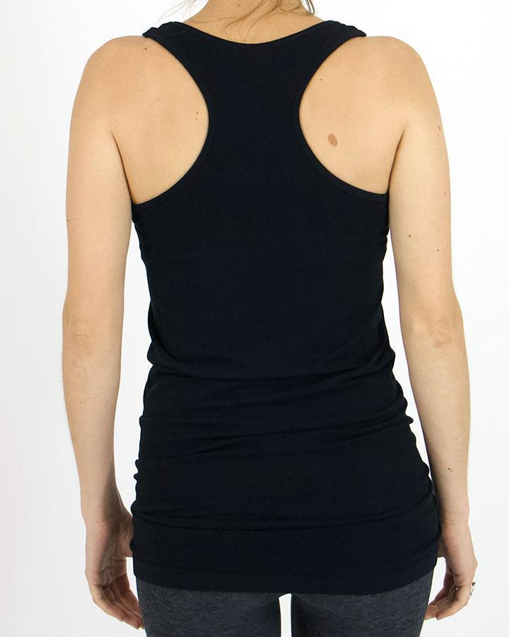 Back view of model wearing the black racerback tank top paired with charcoal leggings against white backdrop.