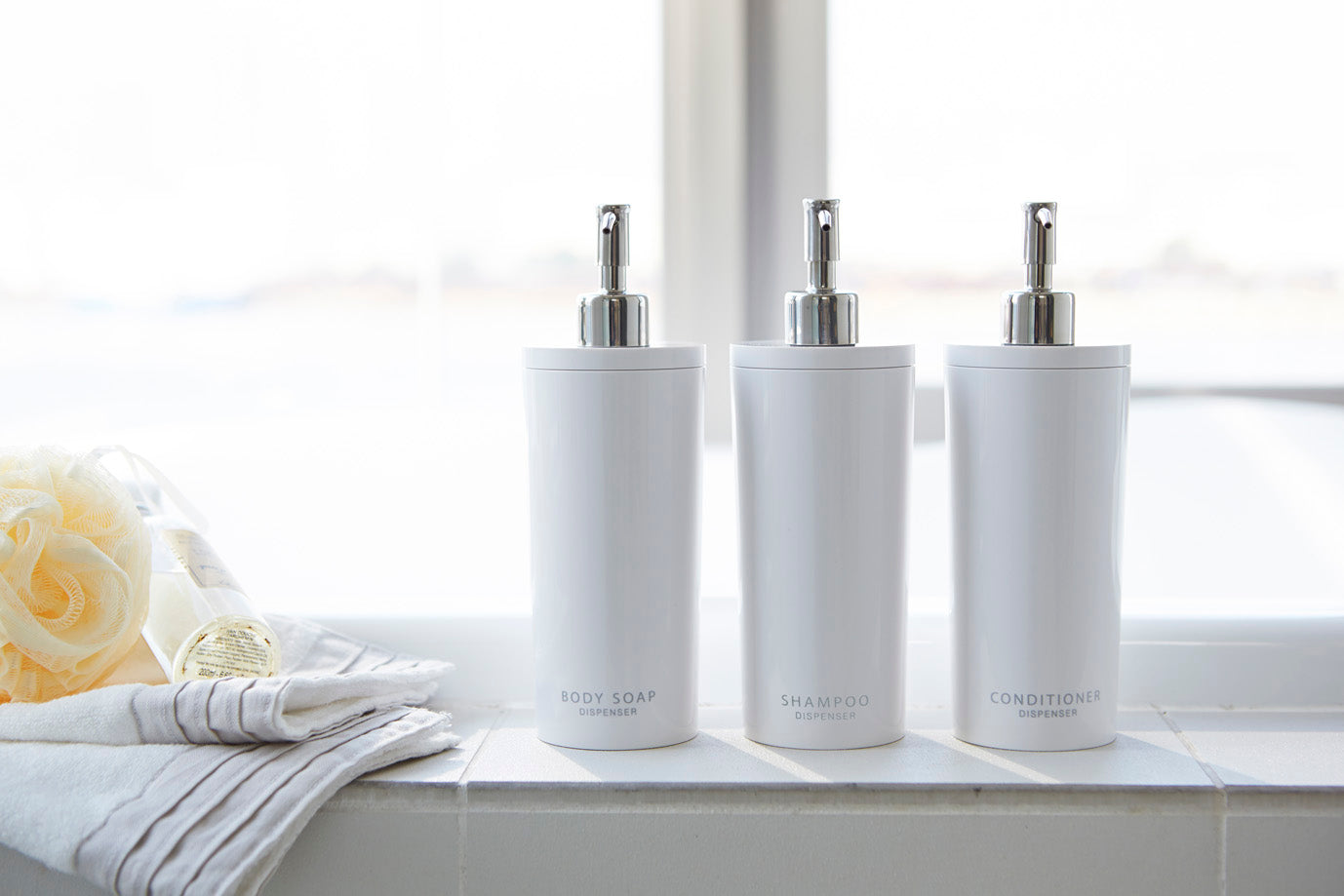 Three of tower soap dispensers in the sunny bathrom