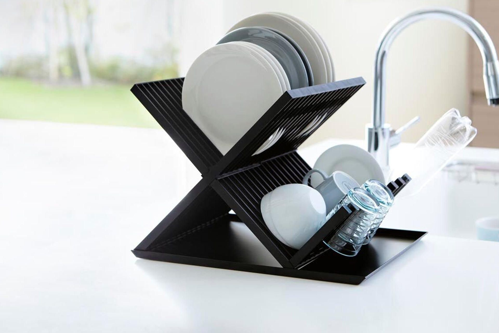 Yamazaki Home Tower X-Shaped Dish Rack holding plates, cups and glasses on the counter