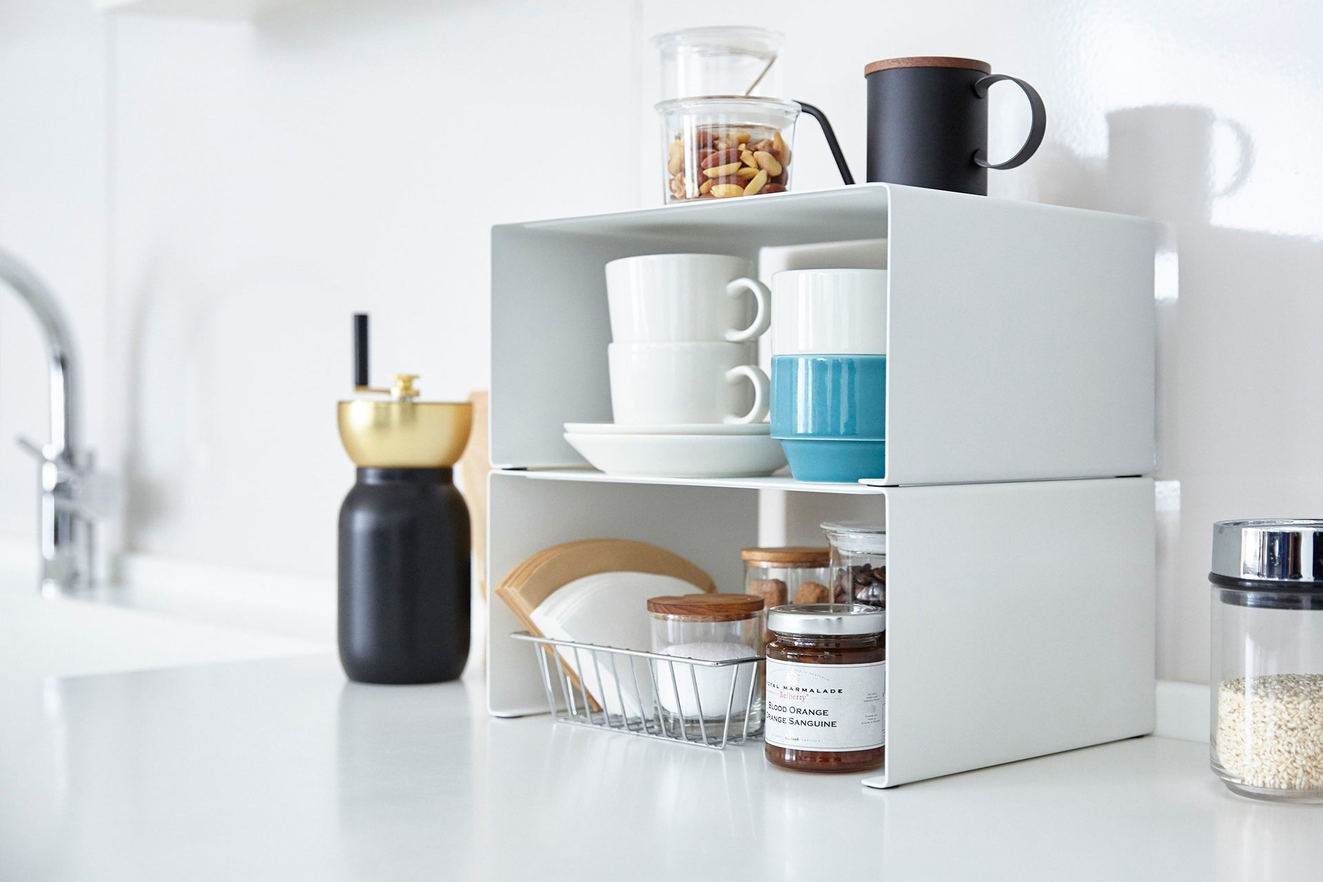 Two of Yamazaki Home Tower Stackable Litchen Rack is stacked and accomodating mugs, plates and some kitchen stuffs.