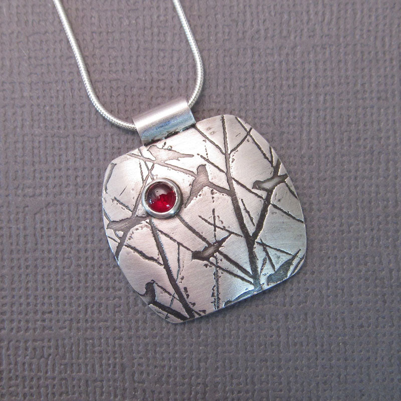 Handmade sterling silver bird pendant with red gemstone