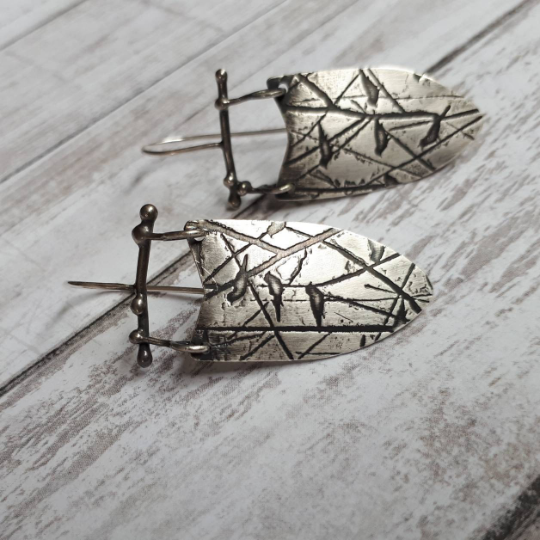 Shield-shaped earrings with bird and tree pattern